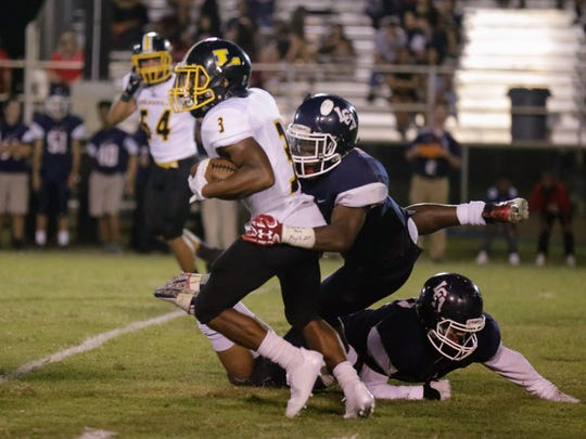 Lafayette Christian linebacker Martin Lee III wraps up Loreauville's Brennon Williams in the second quarter of the Knights' 55-13 win on Friday, September 8, 2017.