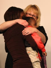 Desiray Thompson and her daughter Astoria Boone are hugged by Deb Dachille during graduation from Monroe County's Nurse-Family Partnership program.