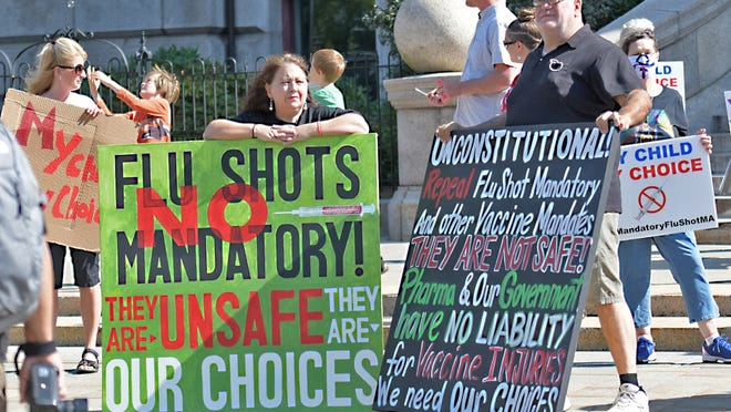 People gather in front of Worcester City Hall to protest the state-mandated flu shots for children on Saturday.