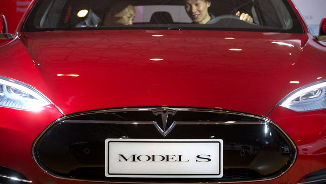 A man sits behind the steering wheel of a Tesla Model S electric car on display at the Beijing International Automotive Exhibition in Beijing.