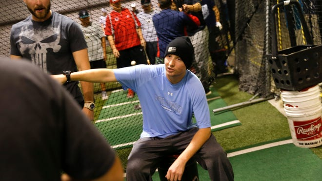 Justin Solomon works helps coach young baseball players on Wednesday at The Strike Zone in Farmington.
