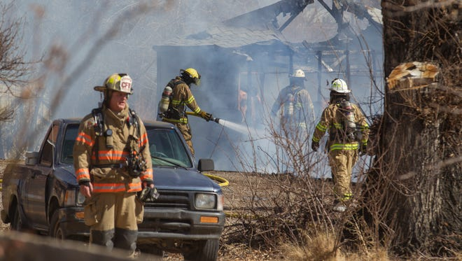 San Juan County Fire Department firefighters work to contain a structure fire on Wednesday on County Road 3535 in Flora Vista.