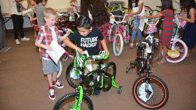 Noah De Leon, a second grader, maneuvers his bicycle from the rest of the bikes that were donated to Gadsden Independent School District elementary students for their academic performance in the second semester.