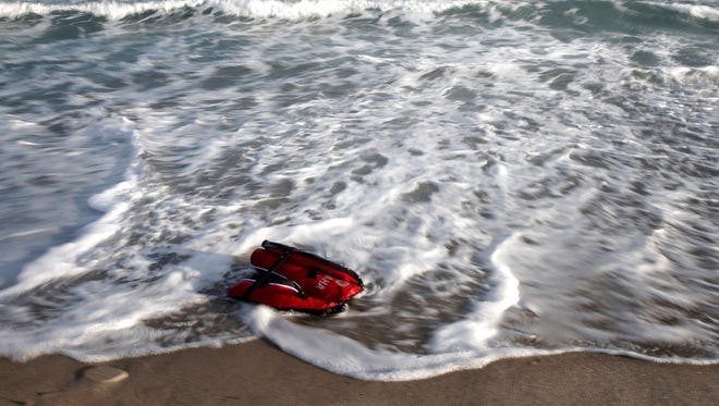 A life vest worn by one of six migrants who crossed from Turkey to Greece with an inflatable boat floats on the shore of Kos island, Greece, May 30, 2015. Greece and Italy are the main points of entry into the European Union for refugees from the Middle East and Africa. According to government estimates, some 37,500 immigrants and asylum seekers have reached Greece illegally so far this year.