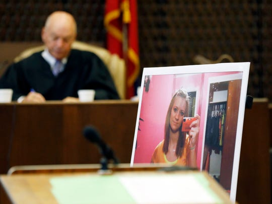Circuit Judge Gerald Chatham, works in the background, while the prosecution presents as evidence a blowup of a selfie of the late Jessica Chambers, during the capital murder trial of Quinton Tellis, 29, who is charged with her burning death, Tuesday, Oct. 10, 2017, in Batesville, Miss. Tellis has pleaded not guilty to murder.