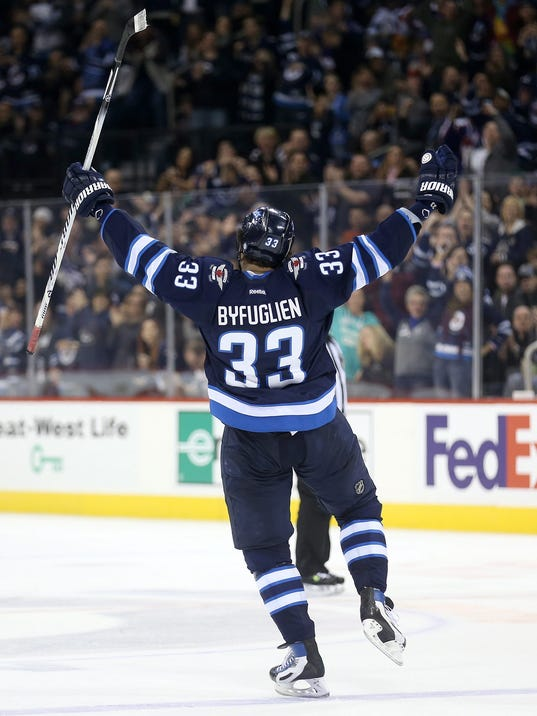 Winnipeg Jets' Dustin Byfuglien (33) celebrates his second period goal against the Dallas Stars' during NHL hockey action at the MTS Centre in Winnipeg, Sunday, March 16, 2014. (AP Photo/The Canadian Press, Trevor Hagan)