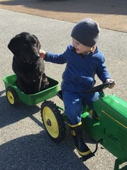 Will Gordon, 4, rides on a play tractor with his dog.