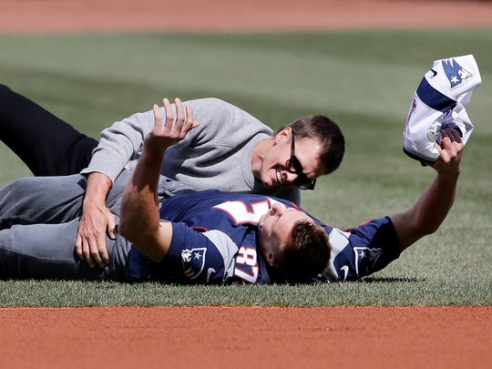 New England Patriots quarterback Tom Brady, top, tackles teammate Rob Gronkowski after he ran with Brady's recovered Super Bowl jersey as they joke around during Boston Red Sox Home Opening Day ceremonies at Fenway Park, Monday, April 3, 2017, in Boston. The Red Sox face the Pittsburgh Pirates in the baseball game.