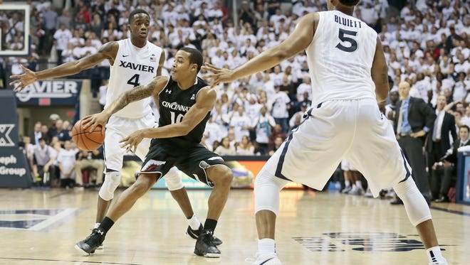 Cincinnati Bearcats guard Troy Caupain (10) throws a pass in the second half of the 83rd annual Crosstown Shootout NCAA basketball game between the Xavier Musketeers and the Cincinnati Bearcats at the Cintas Center in Cincinnati Saturday, Dec. 12, 2015. The Musketeers took a 65-55 win, extending its streak to three in the rivalry matchup.