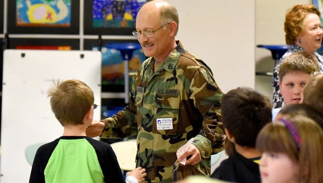 Retired National Guard Sgt. 1st Class Kendall Driver receives hugs from a students, one after another, following a Veterans Day assemble at Verona Elementary School on Wednesday, Nov. 11, 2015. Driver was a guidance counsellor at the school until he retired.