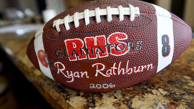 A football with the initials of Riverheads High School as well as Ryan Rathburn's name and jersey number on it. He suffered three concussions while playing football at the school. One occurred playing junior varsity football in 2003 with a second during a varsity game in 2005 and a third in practice that same year.