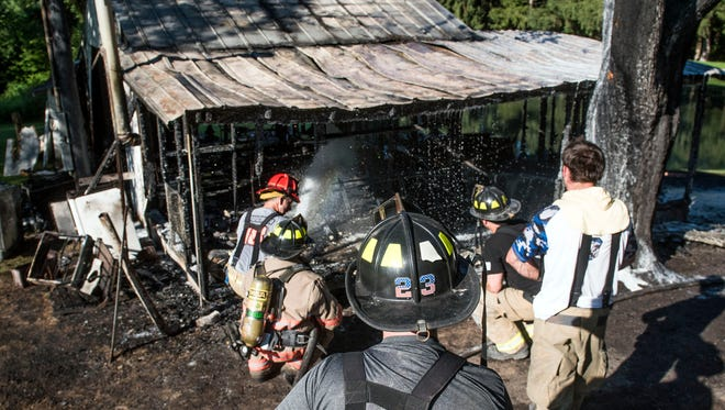 Fire fighters foam down the remains of the recreational structure that was deemed a complete loss in Union township, Sunday, July 30, 2017. The fire originated from cooking, Alpha Fire Company Justin Myers said.