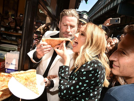 """John Travolta feeds wife Kelly Preston a slice at Lenny' Pizza, the Brooklyn restaurant made famous by """"Saturday Night Fever"""" in 1977."""