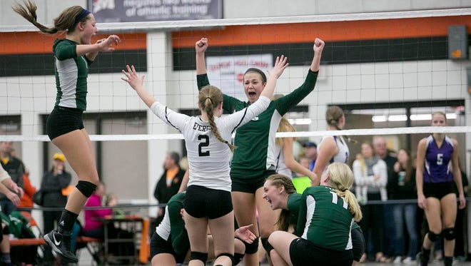 The D.C. Everest volleyball team celebrates their 3-1 victory against Eau Claire Memorial in the Division 1 volleyball sectional semifinal playoff game at Marshfield High School, Thursday