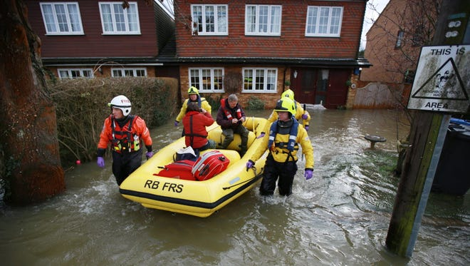 Members of Royal Berkshire Fire & Rescue squad evacuate a family from flooded Wraysbury, England, on Feb. 11.