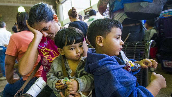 Seydi Maricela Sequeira-Alvarenga, 23, and her children Olvin,1, and Oliver, 3, wait at Greyhound bus station in Phoenix on June 2. They illegally crossed into the U.S. near McAllen, Texas.