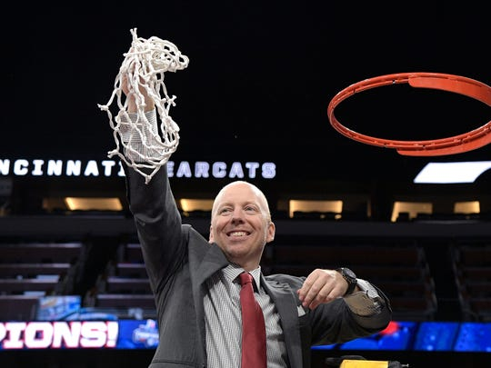 Cincinnati head coach Mick Cronin holds the net toward
