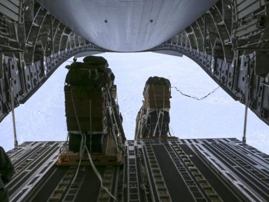 U.S. Navy equipment is airdropped from an Alaska Air National Guard transport aircraft for Ice Exercise 2018.