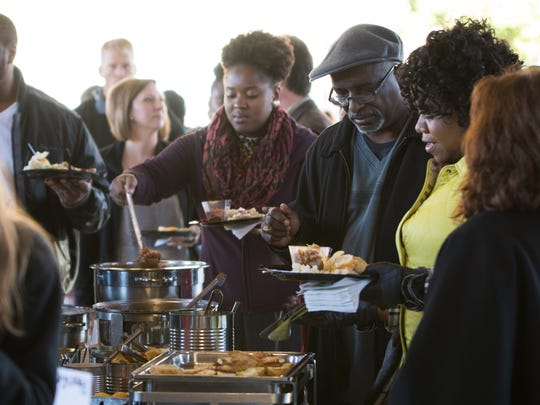 Community members grab food before BC Vision's 100-day celebration begins at Festival Market Square on Wednesday evening.