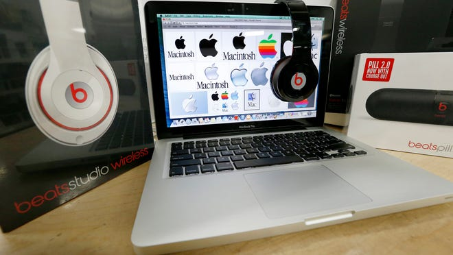 Beats Audio equipment is arranged for a photo next to an Apple laptop at Best Buy in Boston, Friday, May 9, 2014. Apple is orchestrating a $3.2 billion acquisition of Beats Electronics, the headphone maker and music streaming distributor founded by hip-hop star Dr. Dre and record producer Jimmy Iovine, according to a Financial Times report published late Thursday, May 8, 2014. (AP Photo/Michael Dwyer)