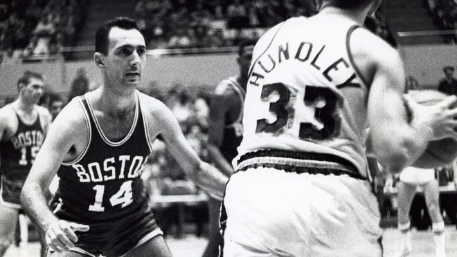 In this Feb. 22, 1961 photo from Los Angeles, Boston Celtics guard Bob Cousy (14) defends Los Angeles Lakers guard Rod Hundley (33) at the Forum.