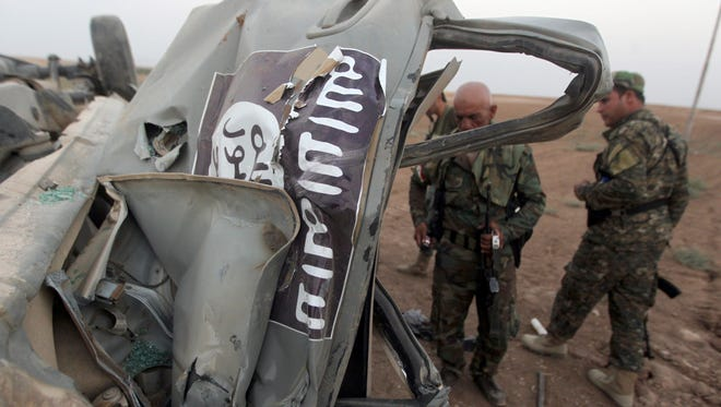 Peshmerga fighters inspect the remains of a car bearing an image of the trademark jihadist flag, which belonged to Islamic State (IS) militants after it was targeted by an American airstrike in the village of Baqufa, north of Mosul, on Aug 18.