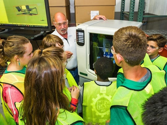 Bill Winiarski, a design engineer for Alpha USA in Livonia, shows students the workings of a 3-D printer.