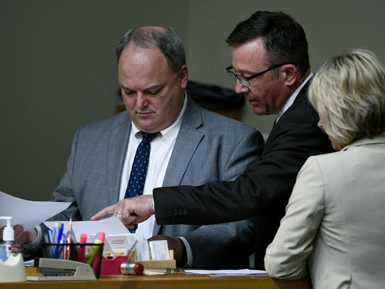 During a break defense attorney Wesley Stone, center,