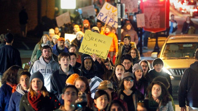 Protestors carry signs and chant slogans as they march along University Avenue on The Corner, a popular nighttime destination with bars and restaurants adjacent to the University of Virginia, Saturday night, Nov. 22, 2014, in Charlottesville, Va.