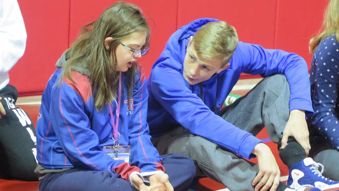 "Washington Township freshman wrestler Nick Flamma talks with Lizzy Pinto on Jan. 9 as the Minutemen hold a clinic on the sport for the Project Unify Club, which seeks to expose young people to ""cultures of inclusiveness between special and regular education students."""