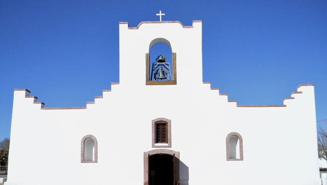 Socorro Mission features a simple, stepped façade and a central bell tower.
