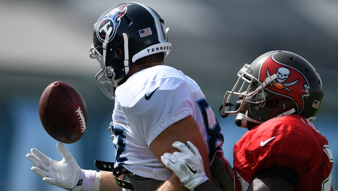 Titans tight end Luke Stocker (88) tries to pull in a catch over Buccaneers defensive back Josh Liddell (22) during a joint practice Wednesday at Saint Thomas Sports Park.