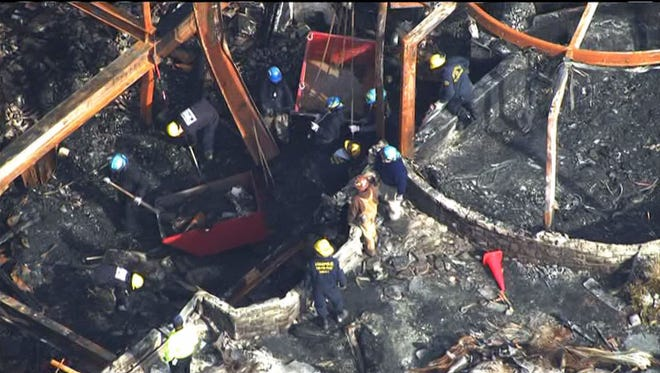 Fire investigators work inside the wreckage Jan. 23, 2015, of an Annapolis, Md., mansion where an intense fire bowed steel beams and caused floors to collapse, trapping the home's owners and their grandchildren inside.