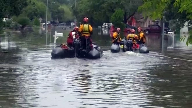 Rescuers from Houston's police and fire departments head toward houses near Hunting Bayou where as much as 4 feet of water flooded homes.