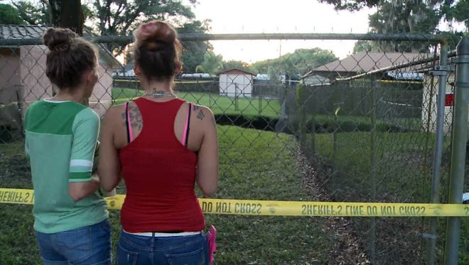 Teens look at a sinkhole Nov. 2, 2015, in Seffner, Fla., from behind a fence that Hillsborough County authorities had installed after some people jumped a shorter fence on Halloween night at the affected duplexes to get a better look.