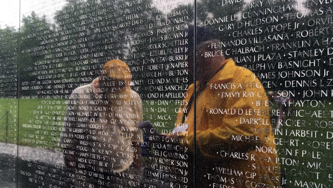 A volunteer, left, and a Never Forgotten Honor Flight veteran are reflected May 22, 2017, in the granite of the Vietnam Veterans Memorial in Washington.