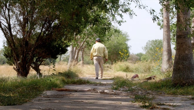 Bob Lucio, former owner of the Fort Brown Memorial Golf Course, walks along a cart path that is being covered by vegetation since the course close in 2015.