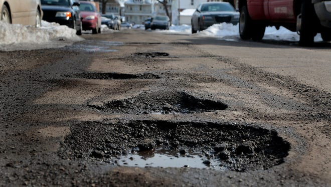 Potholes are scattered along Charest Street in Hamtramck, Mich.
