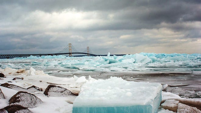Blue ice is piled Feb. 26, 2018, on Lake Huron at the Straits of Mackinac in Mackinaw City, Mich. The Mackinac Bridge is in the background.