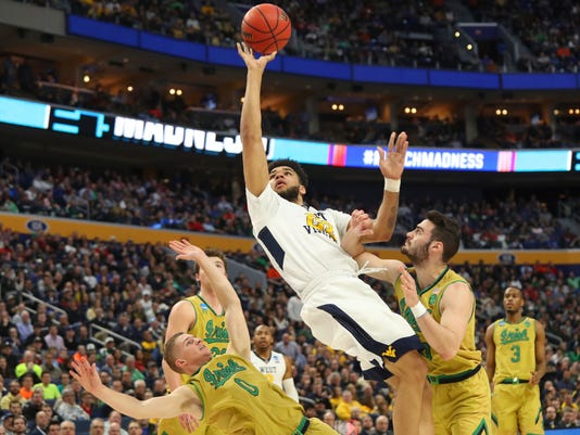 West Virginia forward Esa Ahmad (23) goes to the basket against Notre Dame guard Rex Pflueger (0) and guard Matt Farrell (5) during the first half of a second-round men's college basketball game in the NCAA Tournament, Saturday, March 18, 2017, in Buffalo, N.Y. (AP Photo/Bill Wippert)