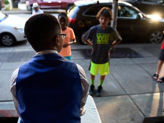 Yohannes Aguayo, 12, performs magic on the Main Street sidewalk July 17, 2016, in Franklin.