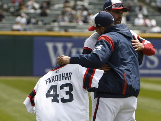 Hector Santiago, left, hugs Chris Volstad as he carries