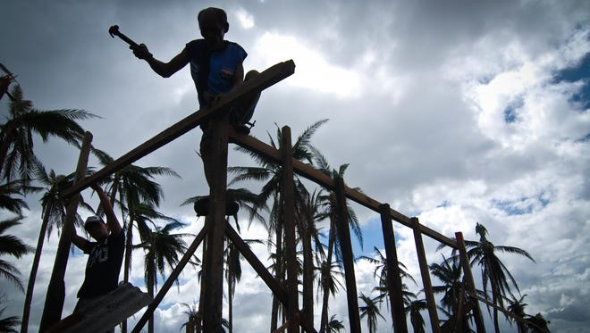 Man in Tacloban, Philippines, tries to rebuild his shanty near the shoreline.