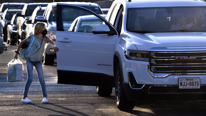 Cars line up in the Wylie West Junior High School parking lot in Abilene to drop students at the fifth and sixth grade entrance Wednesday. The first day of school saw students and faculty wearing masks as they began classes in the midst of a global pandemic.