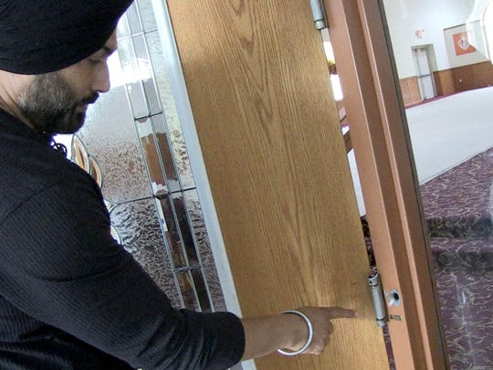 Pardeep Kaleka points to the remaining bullet hole from the shooting that killed six temple members.