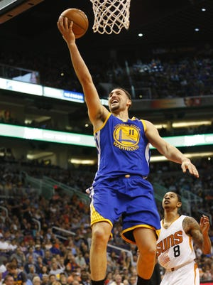 Golden State Warriors guard Klay Thompson (11) lays the ball in past Phoenix Suns guard Tyler Ulis (8) during the third quarter at Talking Stick Resort Arena in Phoenix, Ariz. April 5, 2017.