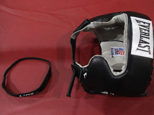 The Linx band rests next to a head gear. Aquinas is helping field test the Linx IAS gear from Rochester-based BlackBox Biometrics that helps coaches, trainers and parents evaluate the concussive forces an athlete my receive in the douse of a game.