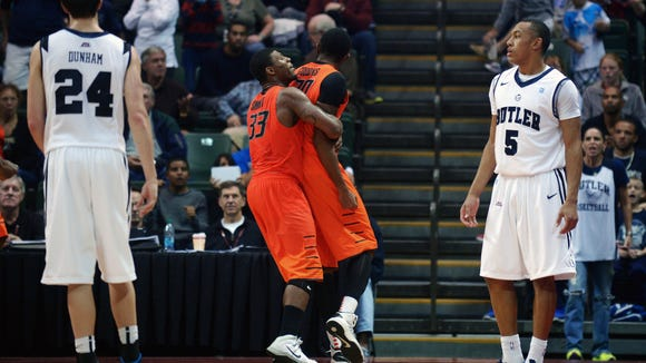 Oklahoma State forward Michael Cobbins, second from right, is congratulated by Marcus Smart (33), as Butler's Kellen Dunham (24) watches, after Cobbins blocked a last-second shot by guard Elijah Brown (5) to preserve a 69-67 victory in an NCAA college basketball game at the Old Spice Classic tournament in Kissimmee, Fla., Friday, Nov. 29, 2013. (AP Photo/Phelan M. Ebenhack)