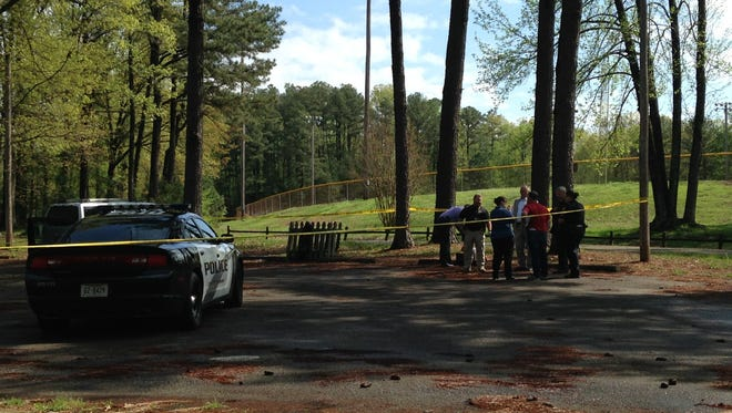Law enforcement officers investigate after a body was found in Muse Park this morning.