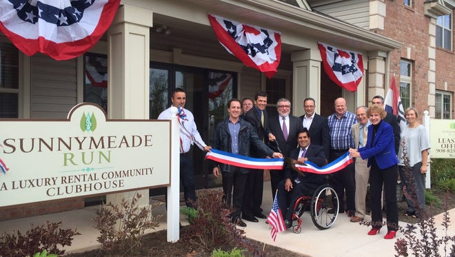 Pictured at Sunnymeade Run, as Freeholder Patrick Scaglione (center) cuts the ribbon at the new clubhouse, are Andrzej Bladek, Jeffrey Hiller, Anatol Hiller and Andy Nowack of Premier Development; Stephen Bearse and Toni Natale of the Hillsborough Economic & Business Development Commission; Hillsborough Business Advocate Gene Strupinsky; Michael Textores of Van Cleef Engineering; and Richard Arzberger, Steve Tietke and Michele Strassheim of Sonnenfeld & Trocchia Architects.